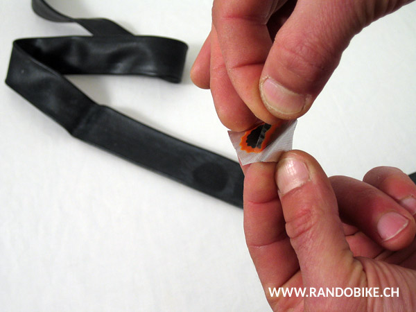 Retirer le film d'aluminium de la rustine. Celle-ci doit rester collée sur le film plastique transparent. Attention à ne pas toucher le côté encollé avec les doigts
