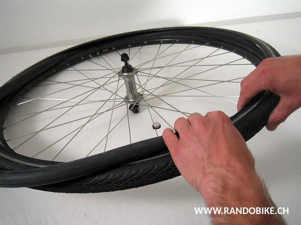 Remettre un flanc du pneu en place sur la jante puis y glisser la chambre à air légèrement gonflée en commençant par mettre la valve dans son trou. Veiller à respecter le sens de rotation du pneu qui, si il y en a un, est indiqué sur son flanc