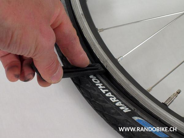 Insérer un premier démonte-pneu entre le pneu et la jante en s'assurant d'être dans l'alignement d'un rayon