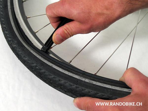 Tenir fermement la roue et pousser le troisième démonte-pneu pour sortir complètement le pneu sur tout le pourtour de la jante