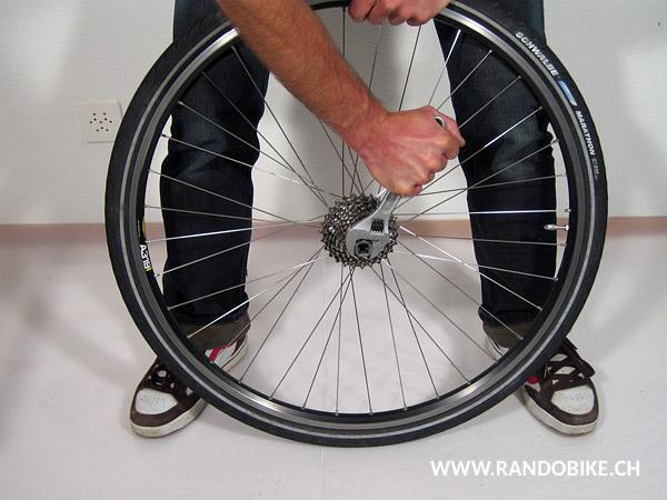 Poser la roue en appui sur le sol et préparer la clé à molette sur le démonte-cassette