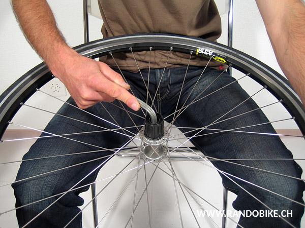 Avant de serrer, empoigner la roue fermement d'une main pour la maintenir