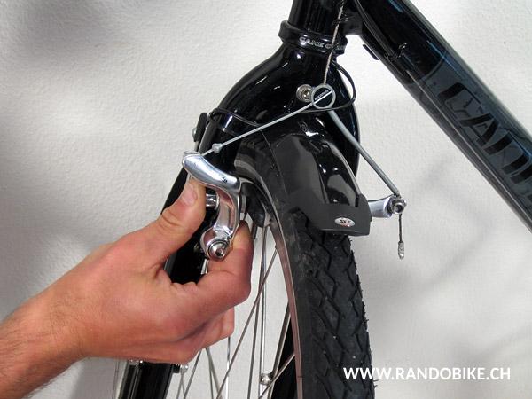 D'une main, appuyer sur l'étrier qui n'a pas d'écrou de blocage du câble jusqu'à ce que le patin touche la jante