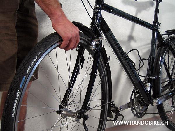 Mettre le roue en position sur la fourche, l'axe bien en place dans les pattes de fixation