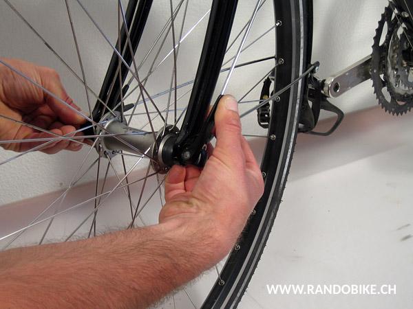 S'assurer que la roue est bien en place sur la fourche et pivoter le levier pour serrer. Bien appuyer pour bloquer la roue