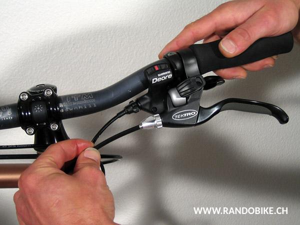 Pour remettre le câble en place dans l'étrier, tirer sur la pipe d'une main en appuyant sur l'étrier de l'autre