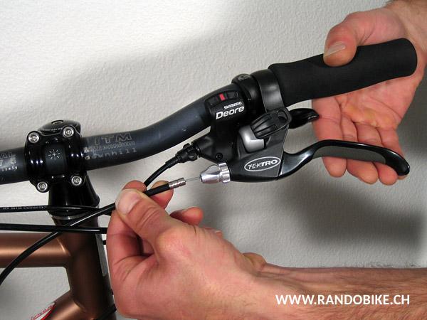 Tirer le câble vers le bas pour le faire passer dans les fentes de l'ajusteur, de son contre-écrou et du levier qui ont été alignées