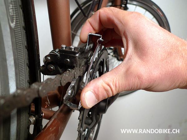 Régler ensuite l'orientation de la cage. Elle doit présenter un défaut d'alignement avec le grand plateau de 1-3 mm vers l'extérieur au niveau de la partie basse (sous le pouce)